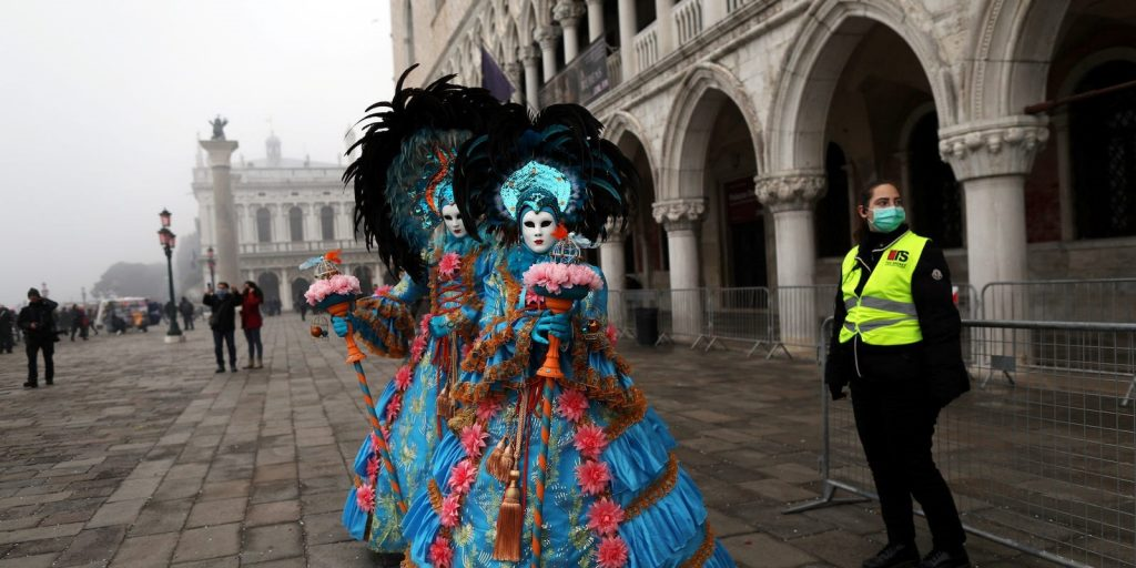 A policewoman next to carnival revelers at Venice Carnival. Ohad Zwigenberg Reuters