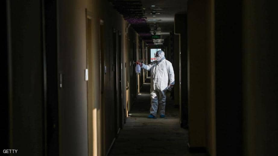 A sanitation worker sanitizes a quarantine area in the affected city